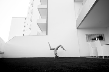 black and white image fine art representing beautiful thin babe female young athlete doing yoga and pilates positions outside home in a garden with all the building in background.