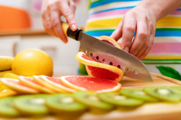 Women's hands Housewives cut with a knife fresh grapefruit on the cutting Board of the kitchen table
