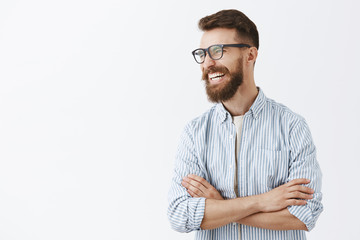 Creative happy and funny bearded man with moustache in glasses with black rim turning left laughing out loud enjoying interesting and hilarious conversation holding hands crossed on chest relaxed Wall mural