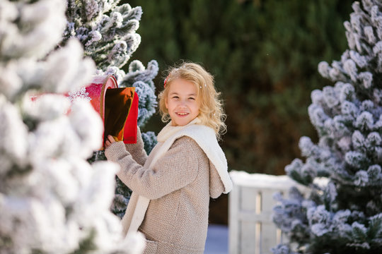 Smiling blonde curly girl with letter near the Santa's mailbox