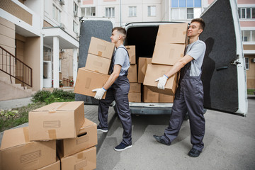 Two young handsome smiling workers wearing uniforms are unloading the van full of boxes. The block...
