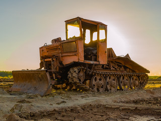 Vintage bulldozer. An abandoned old tractor with on sand quarry. Old tractor in the field
