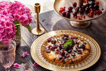 pie with cherries on a wooden table, gold cake