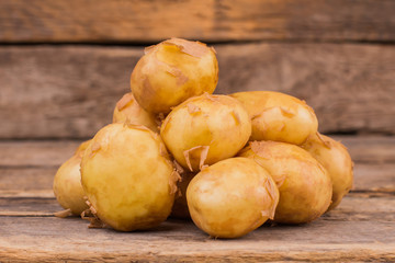 Pile of young potatoes. Wooden desk background.