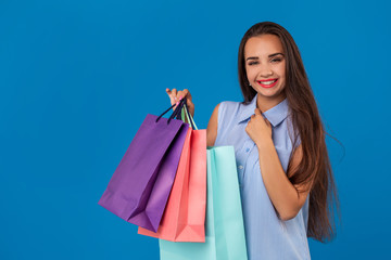 Beautiful young woman with colorful shopping bags on the wonderful blue background