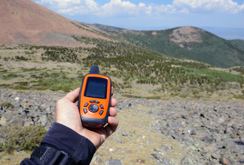 Hiker with handheld navigation unit with mountain background in the wilderness