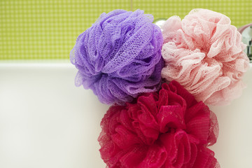 Soft multi-colored bath puff or sponges in bathroom. Copy space. Background, texture