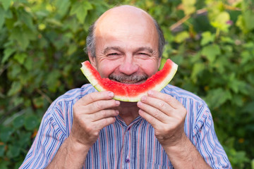 Mature caucasian man with mustache eating juicy water melon with pleasure and smiling.