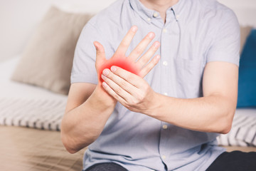 Pain in hand, man suffering from carpal tunnel syndrome at home