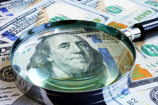 Magnifying glass on dollar banknotes. Finances and exchange.