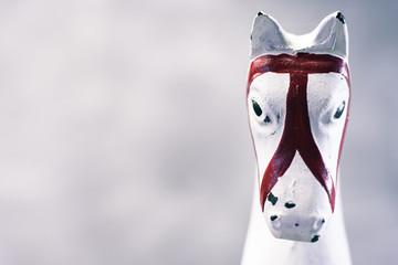 Toy rocking white horse on a dark background, close up.