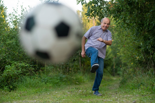 Old man in seventies kicking a soccer ball on playground