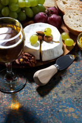 snacks, glass of wine and Camembert cheese on a dark background, vertical, closeup