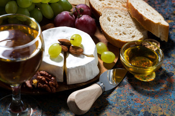 snacks, glass of wine and Camembert cheese on a dark background, closeup