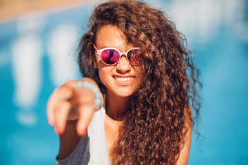 Closeup portrait of effective girl with long curly hair smiling to camera having fun on the beach, dancing and smiling, vacation mood.Nice laughing girl