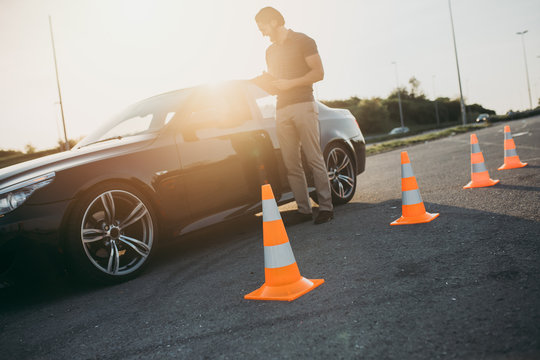 Driving school or test. Beautiful young woman with instructor learning how to drive and park car between cones.