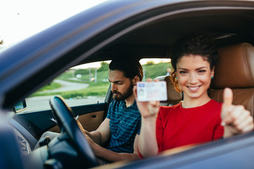 Driving school. Beautiful young woman successfully passed driving school test. She is sitting in car, looking at camera and holding driving license in hand.