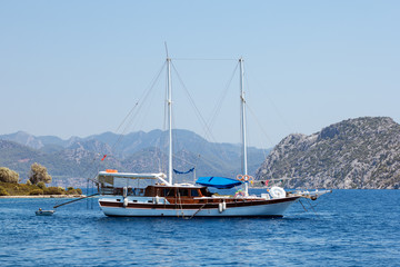 White yacht with wooden deck in the blue sea surrounded by islands on tourism vacation