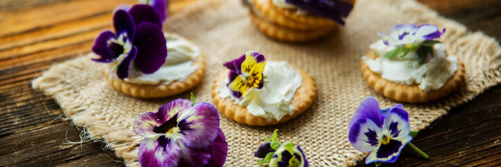 Sandwich with herb and edible flowers butter on wooden background, healthy food.