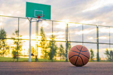 Basketball court. A basketball ball lies on the ground in the background of a shield and an evening sky