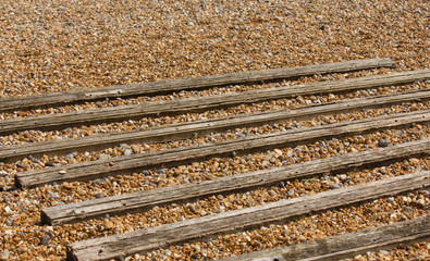 wooden slats on a pebble beach for boat beaching