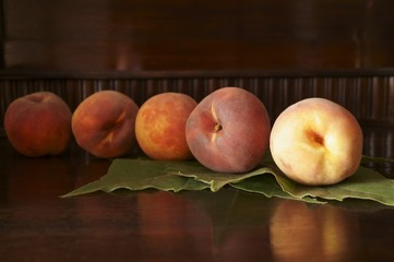 Fresh peaches on a dark background and green leaves