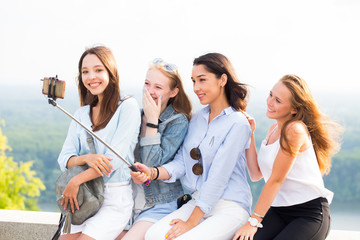 Cheerful group of young smiling women makes a selfie on the background of nature