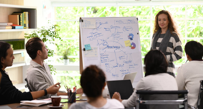 Young business woman giving presentation on future plans to his colleagues at office