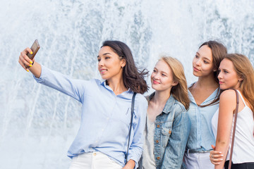 A group of young attractive girls of students makes a selfie on the background of a beautiful fountain