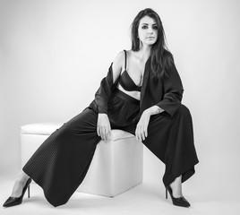 bellissima ragazza mora posa in studio fotografico con pantaloni neri e intimo