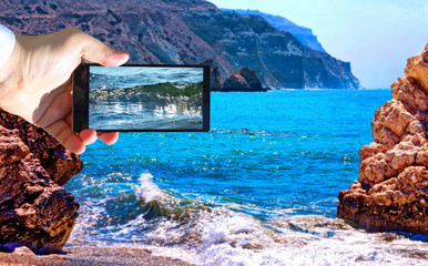 High contrast vibrant image of famous blue emerald sea bay near the birthplace of Aphrodite of Cyprus in summer 2018 with human hand and smart phone