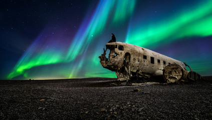 Northern lights over plane wreckage in Iceland Wall mural