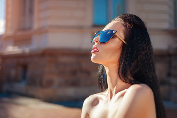 Outdoor portrait of beautiful brunette woman with make-up wearing sunglasses. Topless fashion model
