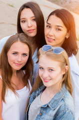 four femle friends looking friendly at camera, smile, happy. people, lifestyle, friendship concept