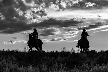Horse wranglers, after the roundup, in silhouette, riding across the plains in Wyoming at sunset in black and white.