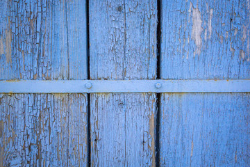 Old weathered wooden plank painted in blue color with metal strip, wooden texture wall background