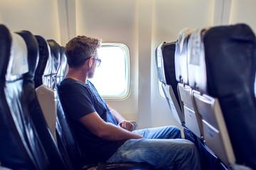 Passenger traveler looking at window in airplane, travel by flight, man tourist sitting in air plane