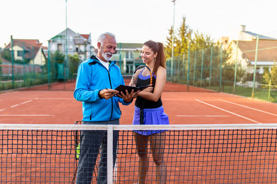 Young female tennis player talking with her coach on the court.