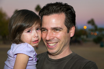 Father Holding His Crying Young Daughter She Has Tears and a Messy Food Face He is Smiling at Someone off Camera