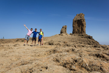 Group of men posing with Roque Nublo on background in Gran Canaria. Friends stand happy after climbing popular natural landmark in Canary Islands, Spain. Adventure, explore, arid landscape concepts