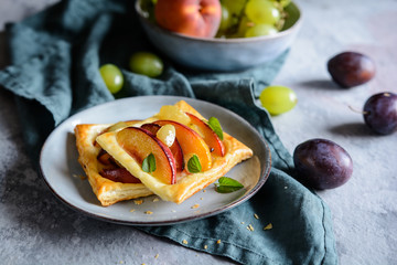 Fruit puff pastry pies with peach, plums and grapes