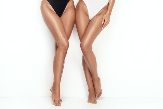 Tanned sexy legs of two girls.