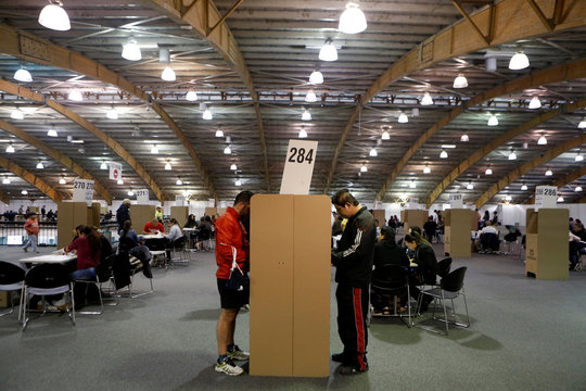 Men vote at a polling station in a referendum of seven questions on anti-corruption measures in Bogota