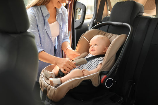 Mother fastening baby to child safety seat inside of car