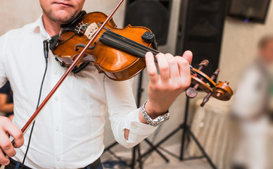 Violin playing viola musician. Man violinist classical musical instrument  fiddle playing on wedding.  Close up young fiddler dressed elegantly playing on wooden violin orchestra . Blurred soft focus