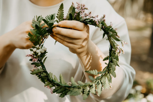 Woman is crafting the wreath of flowers. Beautiful nature floral head crown