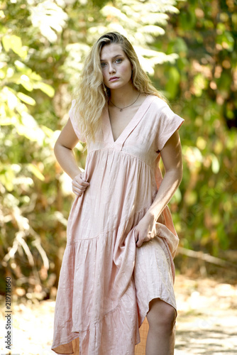 Young blonde teenager modeling outside in summer in sunshine