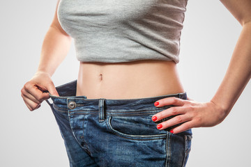 Closeup of slim waist of young woman standing in big jeans and gray top showing successful weight loss, indoor studio shot, isolated on light gray background, diet concept.