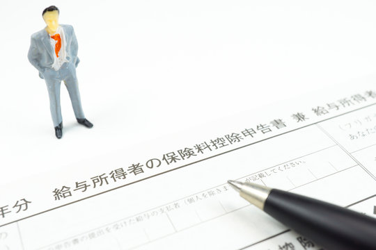 保険料控除申告書と男性の人形