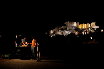 People buy corn from a street vendor as the Propylea are seen in the background atop the Acropolis hill in Athens